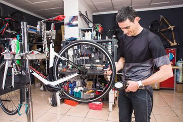 Male involved master is measuring a pressure in tyres of the bicycle in a special workshop