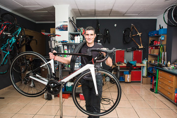 Male involved master is standing towards the bicycle in a special workshop
