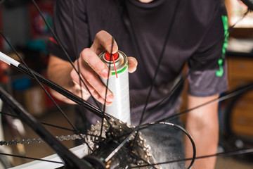 Male hands cleaning and oiling a bicycle chain and gear with oil spray