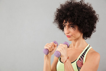 Close up picture of Concentrated curly fitness woman doing exercise