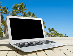 Laptop computer on wooden table. Front palm view. Tropical island background. Open blank laptop computer empty space. Front view with copy space. Empty space for text.