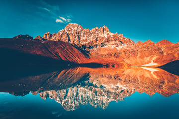 Beautiful snow capped mountain reflected in Gokyo lake in sunset orange glow, blue sky in the background. Trek to Cho Oyu base camp, Khumbu valley, Sagarmatha national park, Nepal. Nature landscape