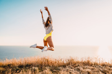 Fashion portrait of jumping happy woman in nature