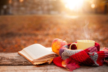Open book, apple and yellow tea cup with warm scarf
