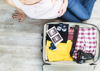 Pregnant woman next to open traveler's bag with ultrasound scan of her baby, baby socks, clothing and photo camera. Travel and vacations concept.