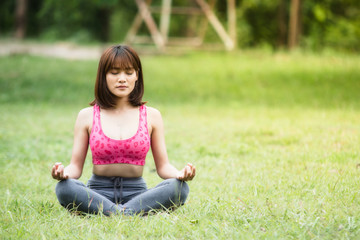 Young girl doing yoga on green grass,Concept of healthy lifestyle and relaxation.