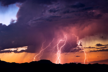 Lightning bolts strike from a sunset storm