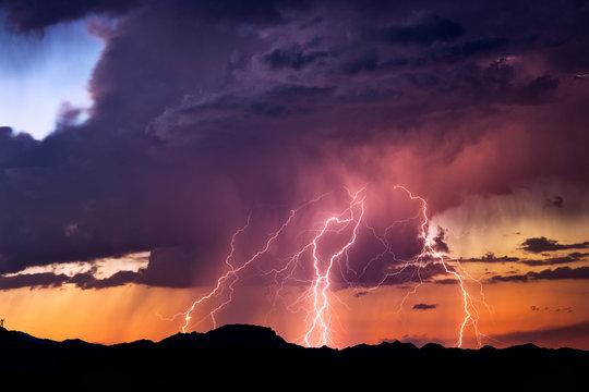 Lightning bolts strike from a sunset storm