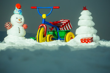Tricycle with present box on snowy background