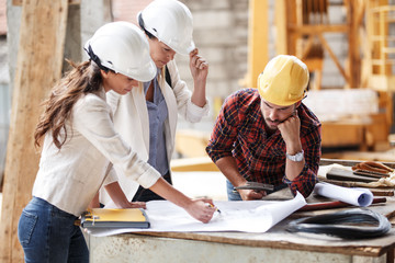 Two female  inspectors and architects discuss with   head engineer about construction project.