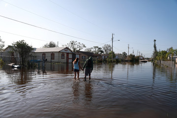 Alyssa Delarosa, left, and Javier Gomez, right, walk down a street that was flooded after the passing of Hurricane Irma in Immokalee, Florida