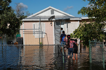 A family arrives at their house, which was flooded after the passing of Hurricane Irma in Immokalee, Florida