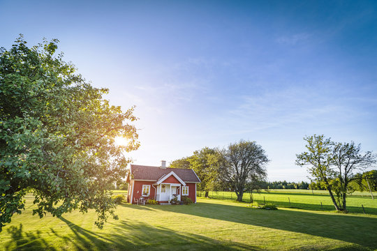 Small red house on a swedish countryside landscape