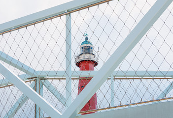 The lighthouse of Scheveningen in Netherlands seen through the gauze of a bicycle bridge