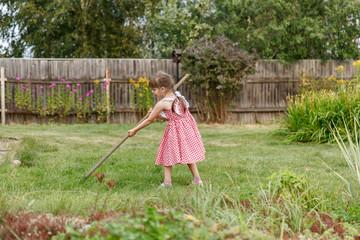 Девочка гребет траву на даче