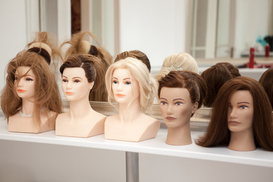 Different mannequin with different hairstyles on a stand. Dummy artificial model