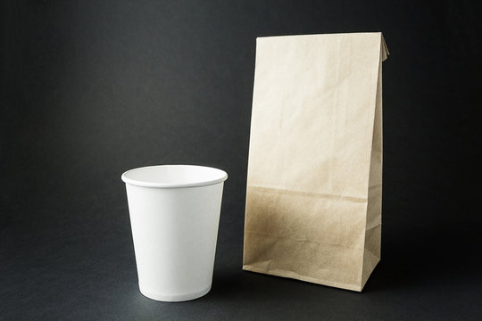 White paper cups and a packing bag from recycled paper layout on a black background, space for text or labels.