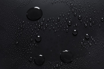 Water drops on a rough black surface