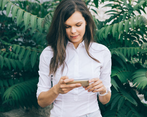 Young woman in a white blouse checks her phone