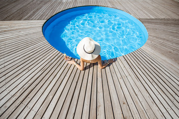 Woman in big sunhat with cocktail drink relaxing at the round swimming pool with blue water outdoors. Top view Fototapete