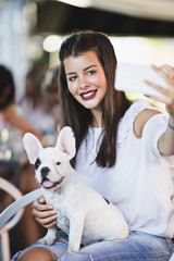 Beautiful young woman sitting in cafe with her adorable French bulldog puppy and taking selfie photo. People with dogs theme.