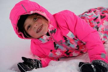 Mädchen liegt im Schnee