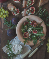 Easy diet salad with arugula, figs and blue cheese on a brown wooden surface. Sandwiches with ricotta, fresh figs, prosciutto, rosemary and blue cheese. Delicious fruity breakfast, top view. Toned