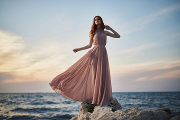 woman in a long pink dress on the beach, sunset