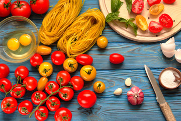 Ingredients for cooking pasta on a wooden table.