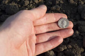 Hand holding Roman denarius (Roman silver coin)