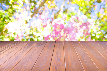 Wood floor with blurred colorful flowers of nature, park garden in summer background , Concept Is For montage product display,design key visual layout background.
