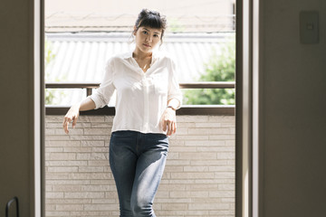 Attractive asian woman enjoying sun light on the balcony