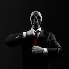 Black and white politician man with skull head in black suit straightens a red tie on black background.
