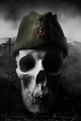 Black and white photo of a human skull in soviet military forage cap on destructed gloomy battlefield background.