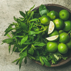 Flatlay of freshly picked organic limes and mint leaves for making cocktail or lemonade in wooden plate over grey concrete stone background, top view, square crop