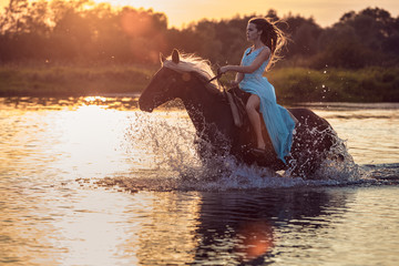Girl riding horse through river water