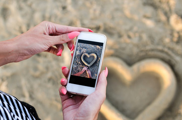 Photography of sand heart with mobile