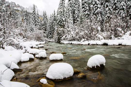 snow covered rocks in a cold mountain river