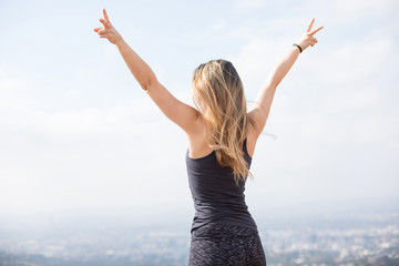 Slender girl standing on the top of the hill showing victory signs with her fingers