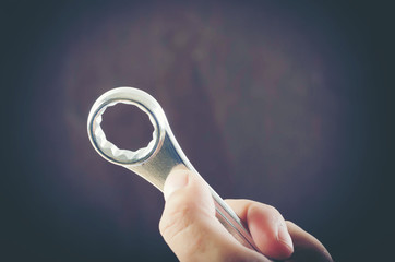 Man's hand holds a wrench isolated on white background.