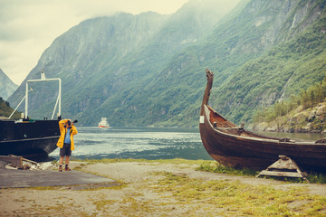 Man taking photo from old viking boat in norway