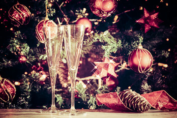 Wall Mural - Getting ready! Two empty glasses with Christmas tree background and sparkles. Holiday season background. Traditional red and green Christmas decoration