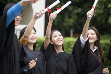 Young Asian Students showing certificate together with Happy emotion at University. People Success for Education Together. Students with Graduation Concept.