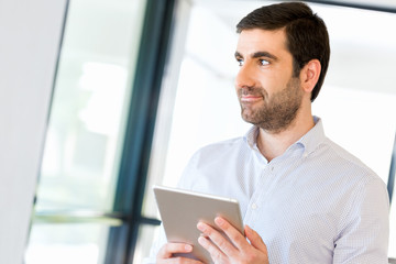 Young handsome businessman using his touchpad standing in office