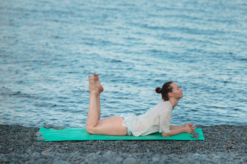 The girl is engaged in yoga on the seashore. Practicing yoga at sea.