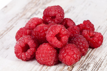 Red fruits of raspberry on wooden plank background, close up
