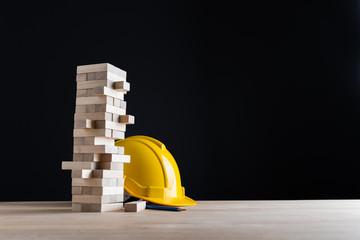 Wood block with yellow safty helmet