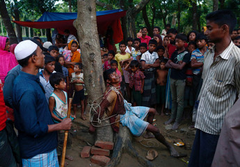 A man accused of stealing money from Rohingya refugees is tied to a tree at a makeshift refugee camp near Balukhali in Cox's Bazar