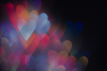 Abstract background of colorful hearts on black. Bokeh of defocused glitters, blurred blue, yellow and pink symbols of love. Festive wallpaper of holidays and celebrations, St. Valentine's day