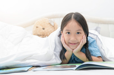 cute girl reading fairy tales on bed